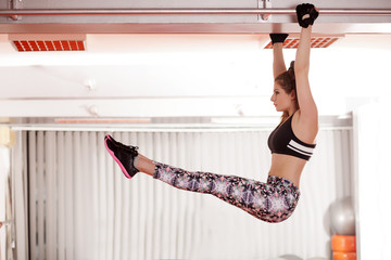 pretty young woman hanging on the dipstick and exercise abs