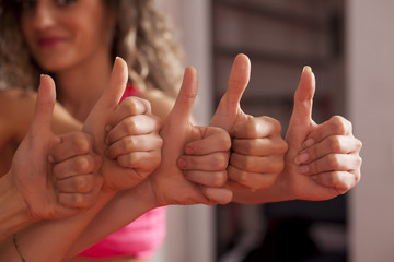 group of young woman showing thumbs up