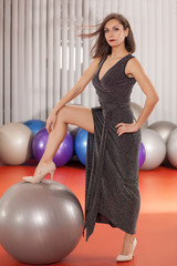 pretty young lady in evening dress posing in fitness center