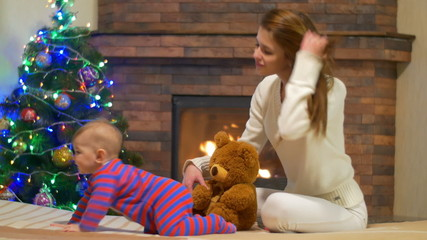 The young girl (mother) with baby at home by the fireplace