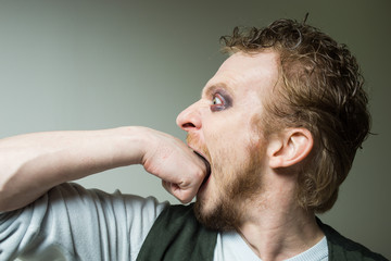 bearded man biting his fist.