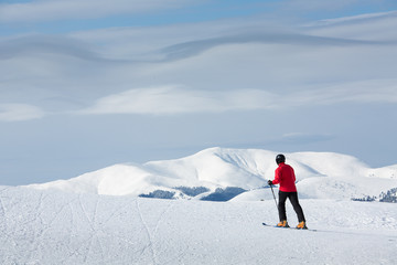 Man walking on ski in mountain with white clouds
