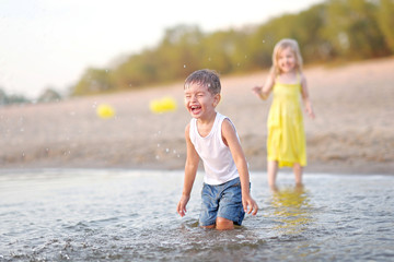 Portrait of a boy and girl on the beach in summer