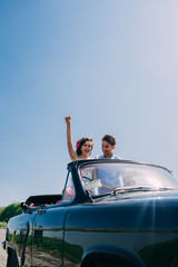 beautiful girl with a guy in a retro car
