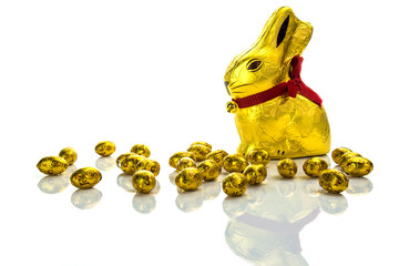 Easter chocolate bunny and golden eggs on wooden table