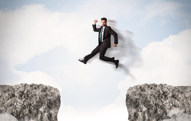 Funny business man jumping over rocks with gap