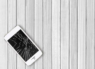 Modern broken mobile phone on white wooden background