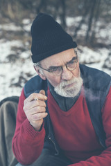 Active elderly bearded man smoking a cigarette