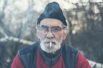 Elderly man enjoying a cigarette outside in winter
