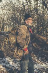Senior man backpacking in winter woods