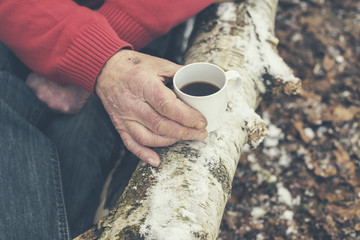 Senior man drinking coffee in a winter forest