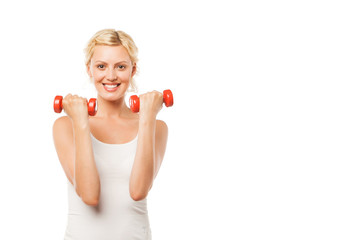 Smiling athletic woman pumping up muscles with dumbbells on