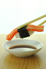 holding crab stick sushi roll with chopsticks and shoyu sauce