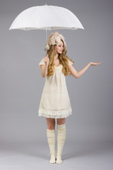 Girl in doll clothes and white umbrella.