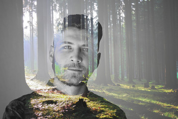 Handsome young  man in double exposure with forrest,
