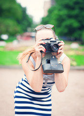 Beautiful young woman in striped dress with old retro camera