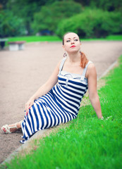 Young beautiful fashionable woman sitting on the lawn