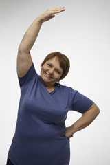 Mature woman making exercise with a gray background