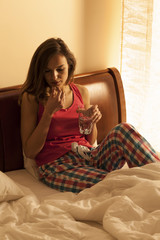 Woman taking pills in bed