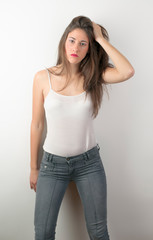 young girl poses in the studio with jeans