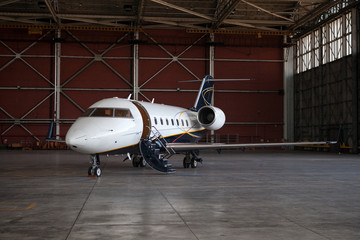 Business jet airplane stays in hangar.
