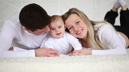 happy family with a baby lying on the bed in the bedroom