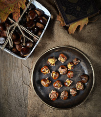 Roasted chestnuts in pan on rustic background