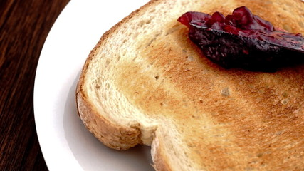Strawberry raspberry jam being spread on toast in slow motion
