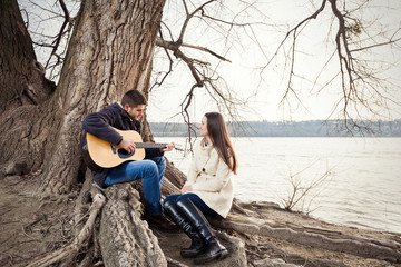 Young guitarist serenading to his girlfriend in nature