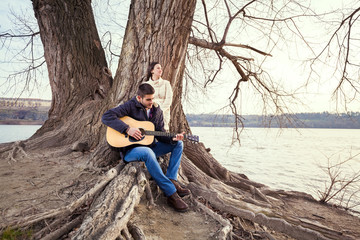 Young couple sitting on a tree and playing guitar
