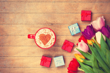 Cappuccino and gifts near flowers