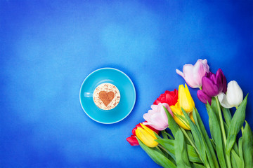 Cup near flowers on blue background