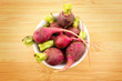 Fresh radishes in bowl against wooden background