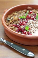 Bowl of granola with pomegranate seeds and yogurt.