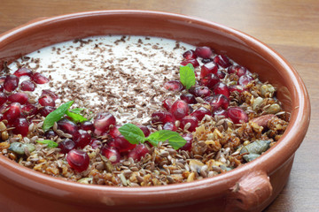 Bowl of granola with pomegranate seeds and yogurt.