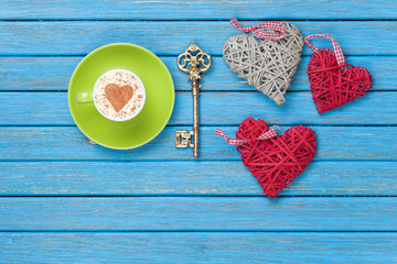Cup of Cappuccino with heart shape symbol, key and toys