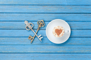 Cup of Cappuccino with heart shape symbol and two keys
