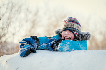 Happy child in winterwear laughing while playing in snowdrift