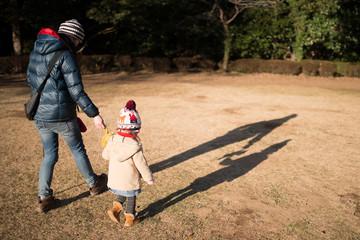 熊の縫い包みと散歩する親子