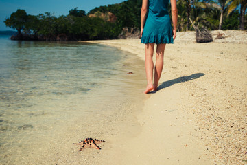 Woman walking past a starfish on beach
