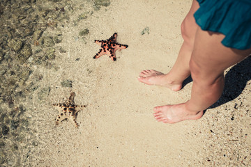 Two starfish and the feet of a young woman