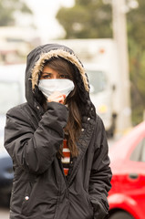 young girl walking wearing jacket and a mask in the city street