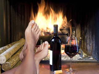 relex with  glass of wine in front of  fireplace