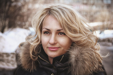 Portrait of a young tanned beautiful girl in winter outdoors