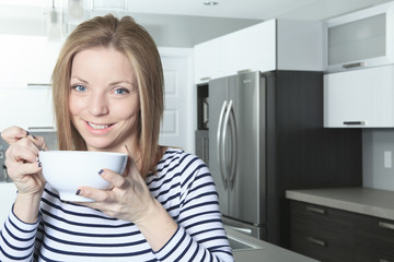 A Jolly woman having breakfast at home