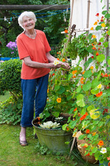 Happy Old Woman Taking Care her Flower Garden.