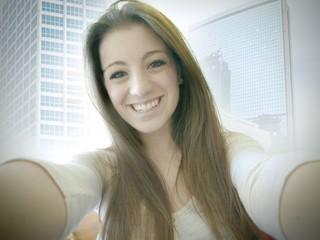 Ragazza sorridente selfie su sfondo di grattacieli