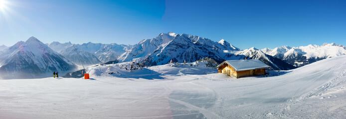 Winterpanorama mit Schifahrern und Schihütte
