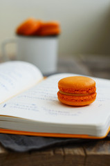 Orange colored macaroon over open diary with notes