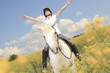 A white horse on yellow flower field with a rider. - 78160392